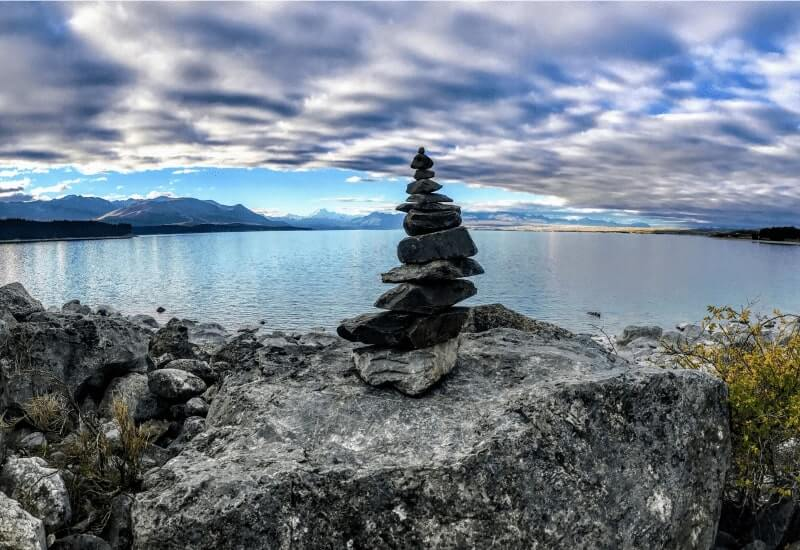 A pile of rocks balancing in front of a lake